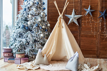 Christmas tree with gifts and wigwam near window in child room, copy space. Christmas decorations. Childen room interior with decorated play tipi tent. Scandinavian style