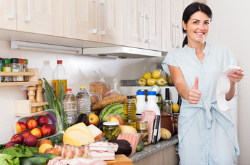 Woman is standing with check and satisfied of the prices of food at home.