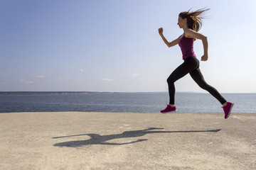 Young beautiful girl jogging and training on the beach