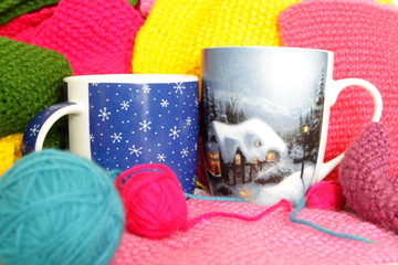 Two cups with winter pics with a drink standing among multicolored threads, knitted pieces and balls of yarn