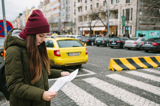 A portrait of a tourist girl or student who is looking at a map on a street in Prague in the winter time and makes her way to the sights or is lost.