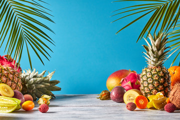 Pineapple, mango, dragon fruit, passion fruit, coconut, carambola, kumquat - frame of exotic fruits with tropic leaves on a blue background.