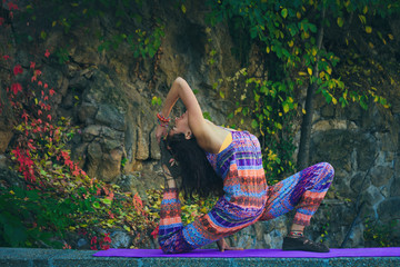 young woman practice yoga outdoor colorful autumn background