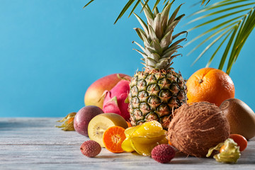 Creative exotic composition with tropical fruits and green leaves pineapple, coconut, mango, kiwi, pitahaya on a wooden table on a blue.