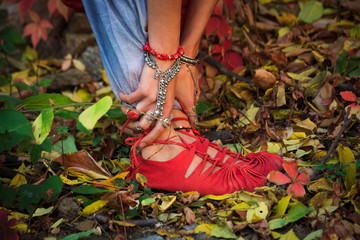 closeup of woman legs and hands in yoga stretch pose in colorful autumn leaves outdoor