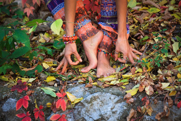 barefoot  woman legs and hands in yoga and mudra gesture in colorful autumn leaves outdoor