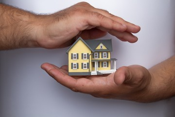Human Hands Holding and Protecting a Model of a House on Grey