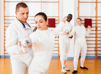 Woman fencer practicing new movements with trainer  at fencing room