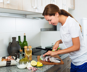Woman cutting fish on kitchen