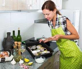 Woman preparing fish on kitchen