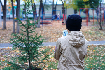 a young boy takes pictures on a mobile phone of a small tree in the Park in autumn