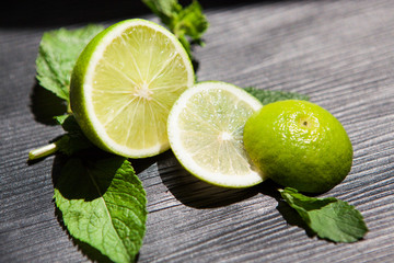 Lime and mint as ingredients for lemonade or mojito, food on black background
