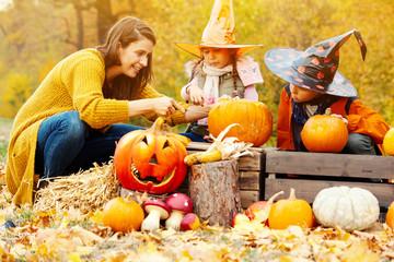 Familie schnitzt gemeinsam Kürbisse für Halloween