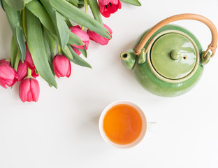 Top view of cup of tea, green tea pot and red tulips with green leaves on white background