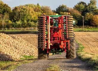 tracteur qui roule dans un chemin prés d'un tas de betteraves aprés la récolte. vu de dos  avec un village en arriére plan