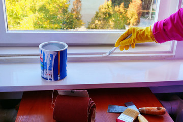 Hand in yellow rubber gloves applies a glossy white  paint finish to a window frame.