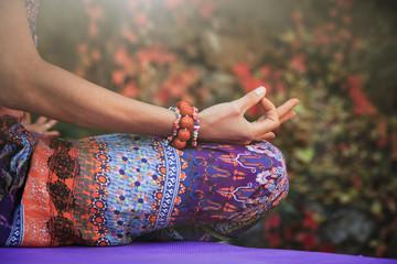 woman practice yoga meditation hands in mudra gesture closeup outdoor