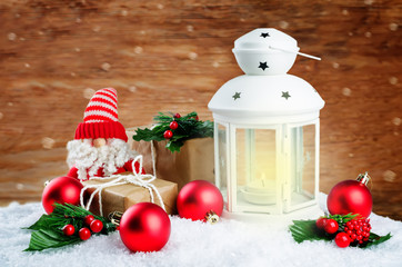 Christmas lantern with gifts, colored balls on a winter wood background