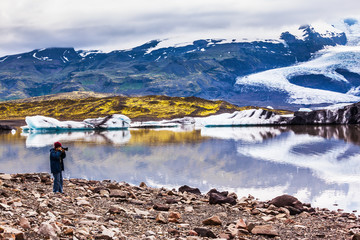 The elderly woman photographs the lagoon