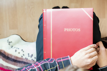 close up hands hold and open red family photo album sitting at home, past memory concept f
