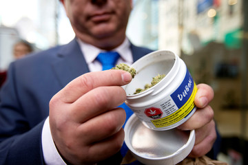 A man shows off his cannabis purchase outside the Quebec Cannabis Society (SQDC) store on the day Canada legalizes recreational marijuana in Montreal