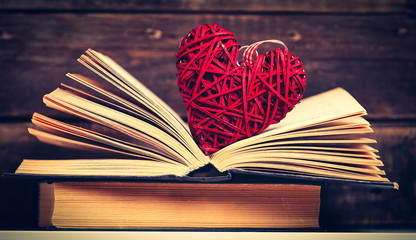photo of the old books and heart shaped toy on the brown wooden background