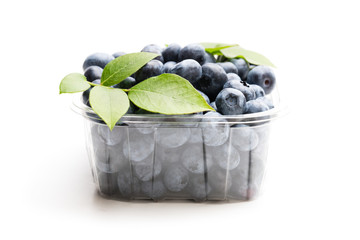 Fresh blueberries in small plastic container isolated on white
