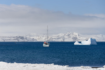 Deurstickers Antarctica Sailing yacht and iceberg in antarctic sea