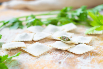 traditional raw ravioli with green and meat on a wooden table with flour, handmade, cooking process
