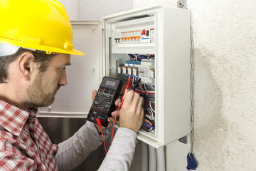 electrician at work measures the electric current