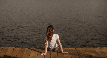 Anonymous female sitting on pier