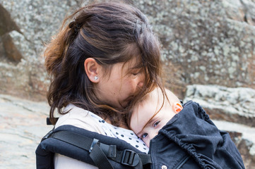 Beautiful young mother with baby child in carrier in the old town. Active travel family vacation
