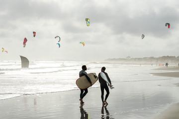 deux surfers marchant sur une plage avec des voiles de kitesurf en fond sous un ciel nuageux