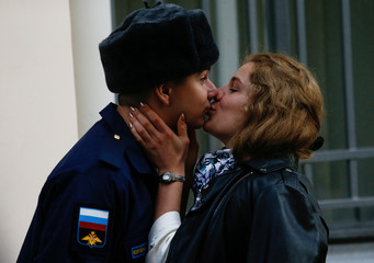 A couple shares a kiss as Russian conscripts depart from a recruiting station in St. Petersburg