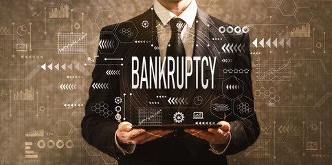 Bankruptcy with businessman holding a tablet computer on a dark vintage background