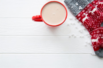 Hot chocolate in red cup and red socks with christmas traditional background on white wooden table background, copy space. Top view.