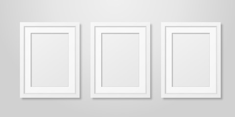 Three Vector Realistic Mofern Interior White Blank Vertical A4 Wooden Poster Picture Frame Set Closeup on White Wall Mock-up. Empty Poster Frames Design Template for Mockup, Presentation