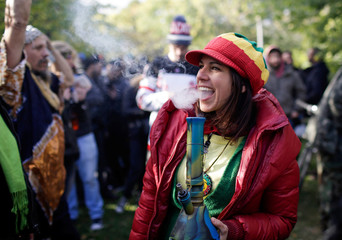 A woman smokes a bong on the day Canada legalizes recreational marijuana at Trinity Bellwoods Park