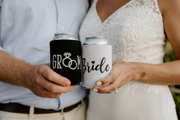 Bride and Groom Holding Matching Mr. and Mrs. Can Koozies On Their Wedding Day