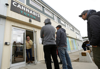 A man reacts as he exits aCannabis Yukon retail store with his purchase while others wait their turn to enter as Canada became the first industrialized nation to legalize recreational marijuana, in Whitehorse, Yukon