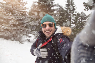 Man with sunglasses taking selfie on snowy day.