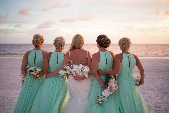 Beautiful Bride and Bridesmaids in Wedding Party Looking out at the Horizon on the Beach During Sunset