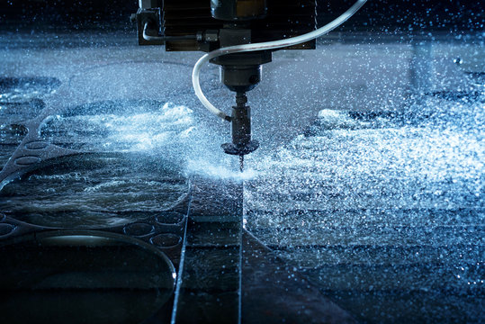 Water jet industrial machine cutting steel plate. Computer controlled metalworking machine using high pressure water jet to cut metal.