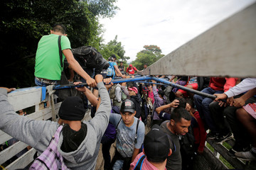 Honduran migrants board trucks sending them back to Honduras, after they crossed the border into Guatemala illegally in their bid to reach the U.S.