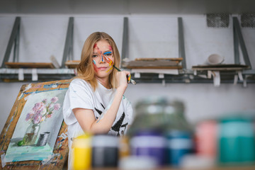 A young attractive artist with a brush in her hands and with a face in the paint stands against the easel with a painting.