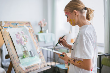A young artist girl with a face and clothes in the paint, paints a picture on the easel.