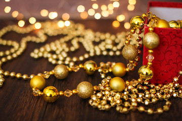 Close up golden christmas decoration balls from red gift box on dark wooden background and bokeh garland
