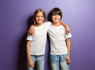 Boy and girl in t-shirts hugging each other on color background Wall mural