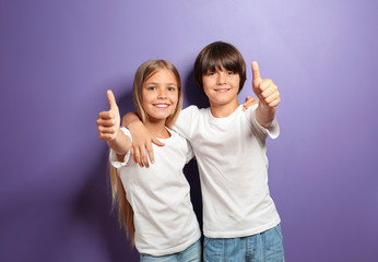 Hugging boy and girl in t-shirts showing thumb-up on color background