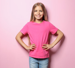 Smiling little girl in t-shirt on color background